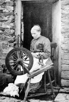 Highland woman spinning outside her house